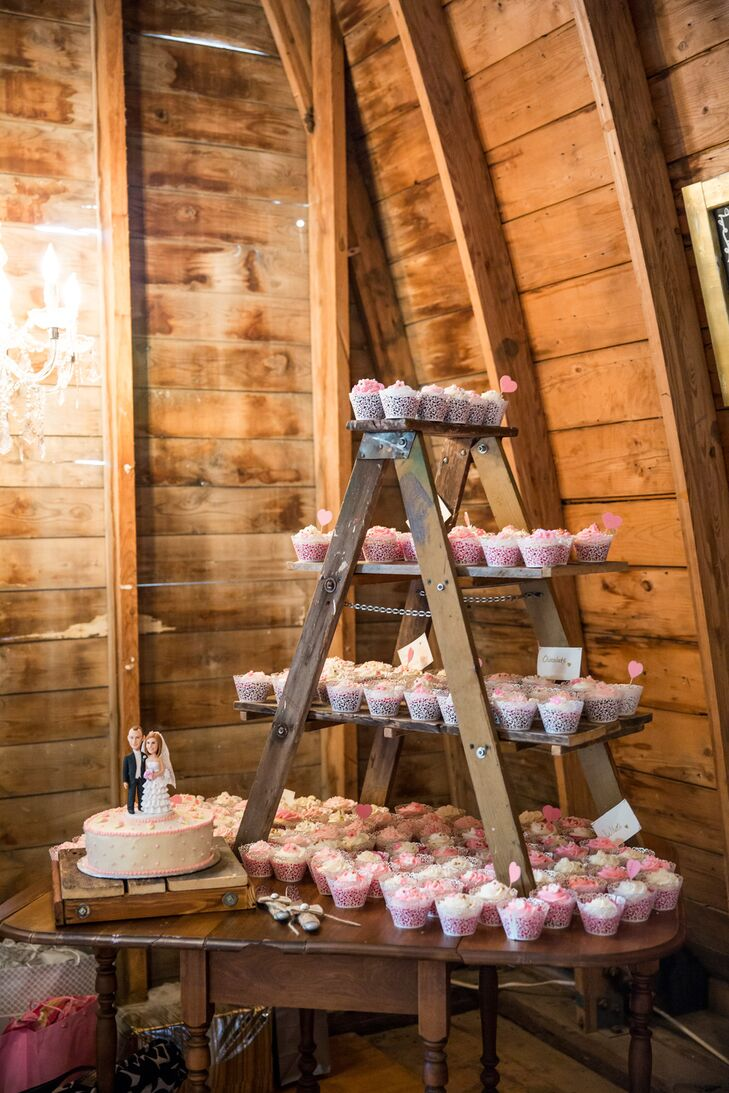 The one-tier cake and cupcakes were displayed on a vintage wooden table. To make more space, Hannah and Caleb set up a rustic wooden ladder on top of the table to make little shelves for the desserts. They wanted this area of the barn to be a little more romantic, so they hung a crystal chandelier next to the display.