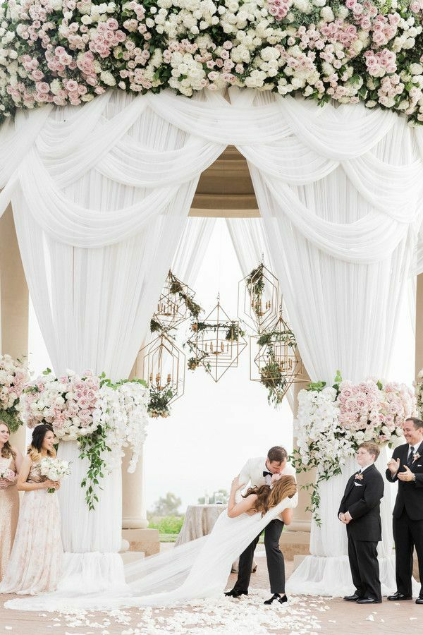 First kiss during wedding ceremony with draping and chandeliers as backdrop