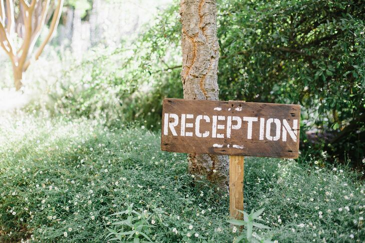 A painted wooden sign pointed guests in the direction of the outdoor reception.