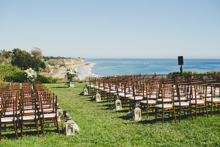 """The ceremony was held at Bacara Resort & Spa's oceanside bluff, which provided a sparkling blue backdrop for the occasion. """"We let the view speak for itself and kept things simple with small arrangements of lanterns and florals,"""" Ivette says. Ivory carriage lanterns and bouquets of pink roses lined the aisle, leading to two stately arrangements of hydrangeas, roses and textured greenery piled high atop refined stone urns."""