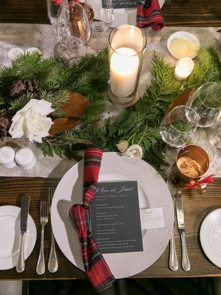 Wintry tablescape with plaid napkins, greenery runner and candles