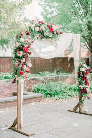 Wood Ceremony Arch With Draping and Bright Red Roses