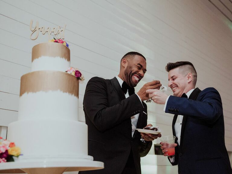 Grooms feeding each other wedding cake at reception