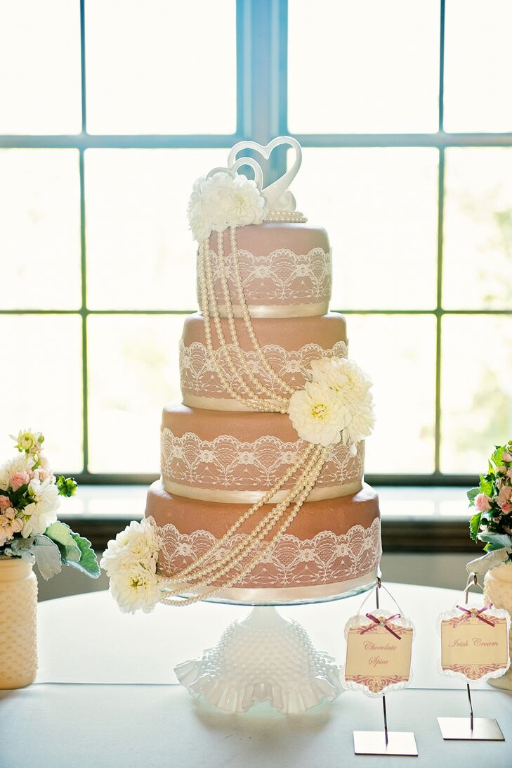 The cake by Rosebeary's Designs in Baking was perfect for the vintage wedding theme. It had four tiers with neutral fondant wrapped with lace and pearl details and scattered ivory flowers.