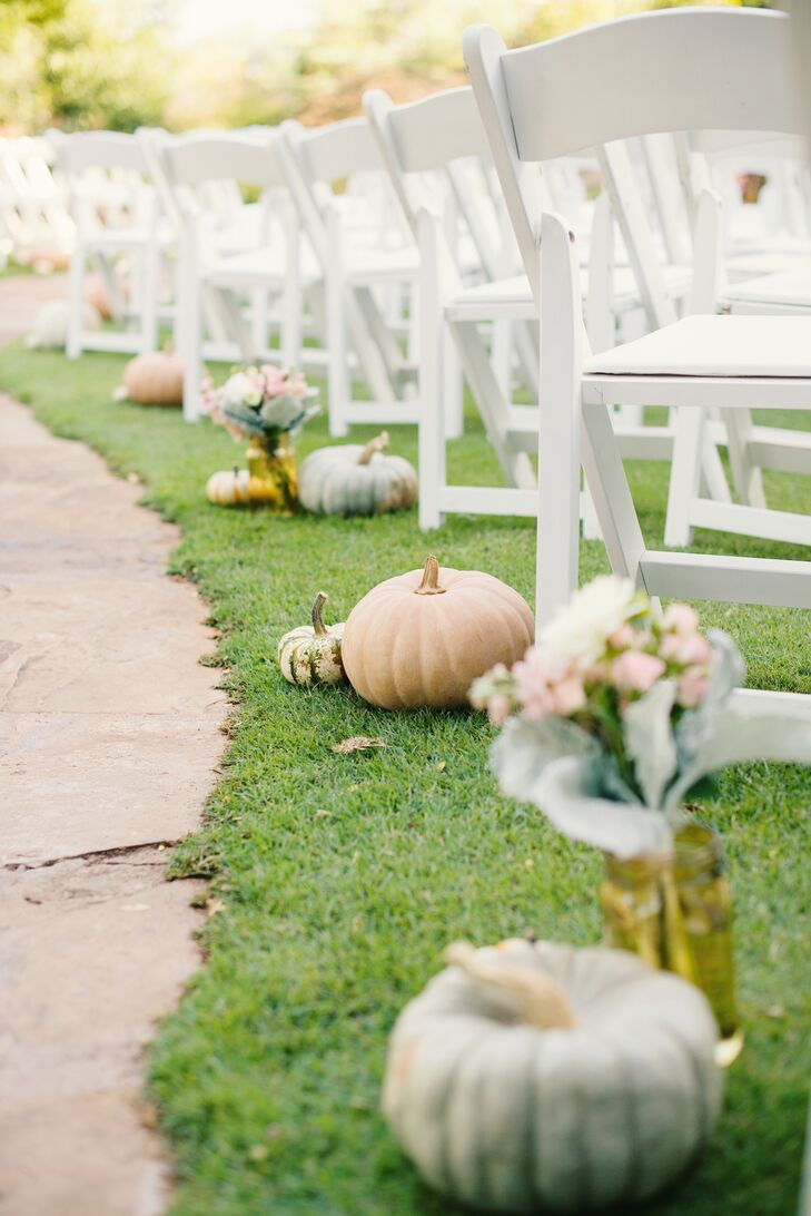Pumpkins and gourds lined the aisle leading to Chelsea and Jeffrey's garden ceremony. Scattered blush and white flowers added to the romantic ambience.