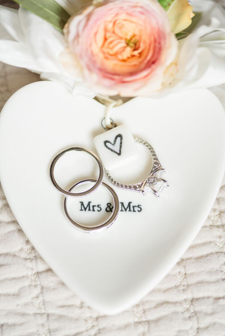 """Andrea and Mariko's wedding rings in a heart-shaped """"Mrs. & Mrs."""" ring dish—rings were designed by Steve Padis Jewelry."""