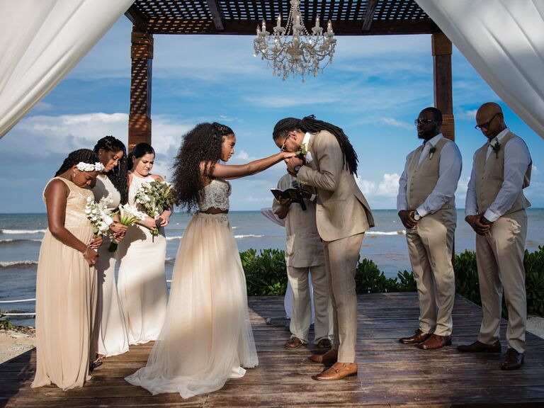 Groom kissing brides hand at ceremony