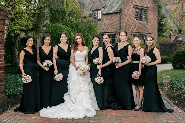 Joelle's bridesmaids wore stunning Noir by Lazaro dresses in black satin. the floor length dresses featured plunging V necklines and cowl backs. Her junior bridesmaid wore a black lace dress.