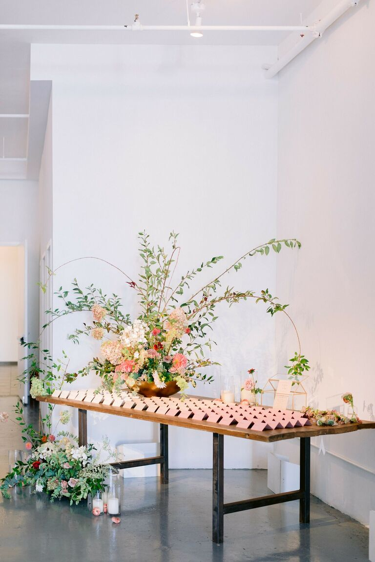 Escort cards and large floral arrangement on table