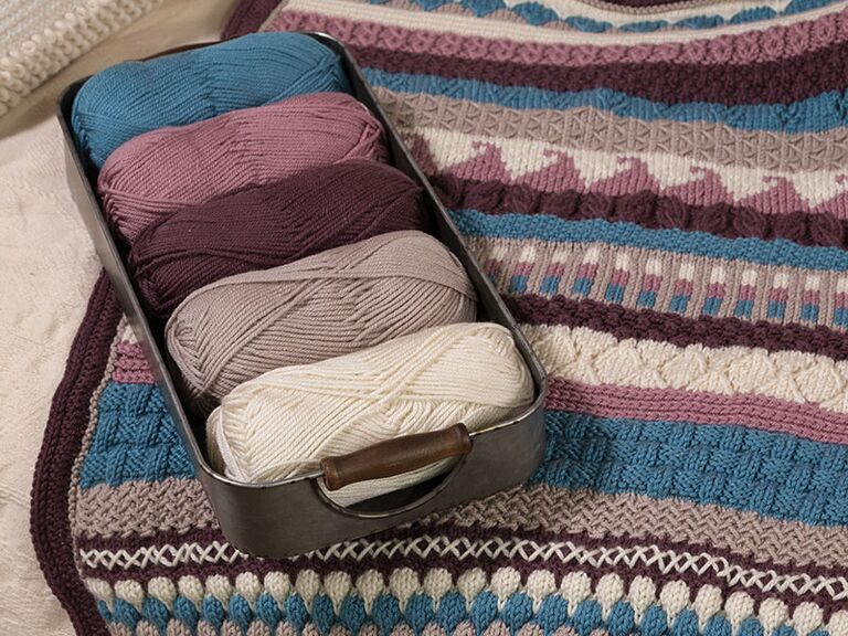 Set of yarn in five different colors on top of knitted striped afghan