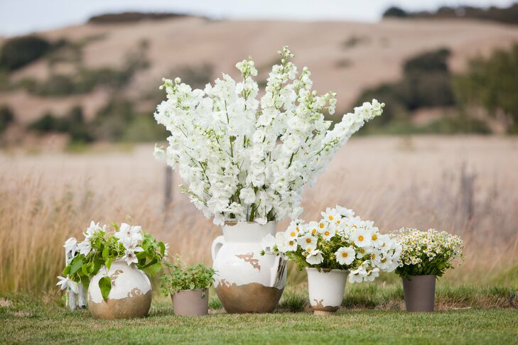 Weathered ceramic pots bursting with seasonal white blooms dotted the ceremony space.