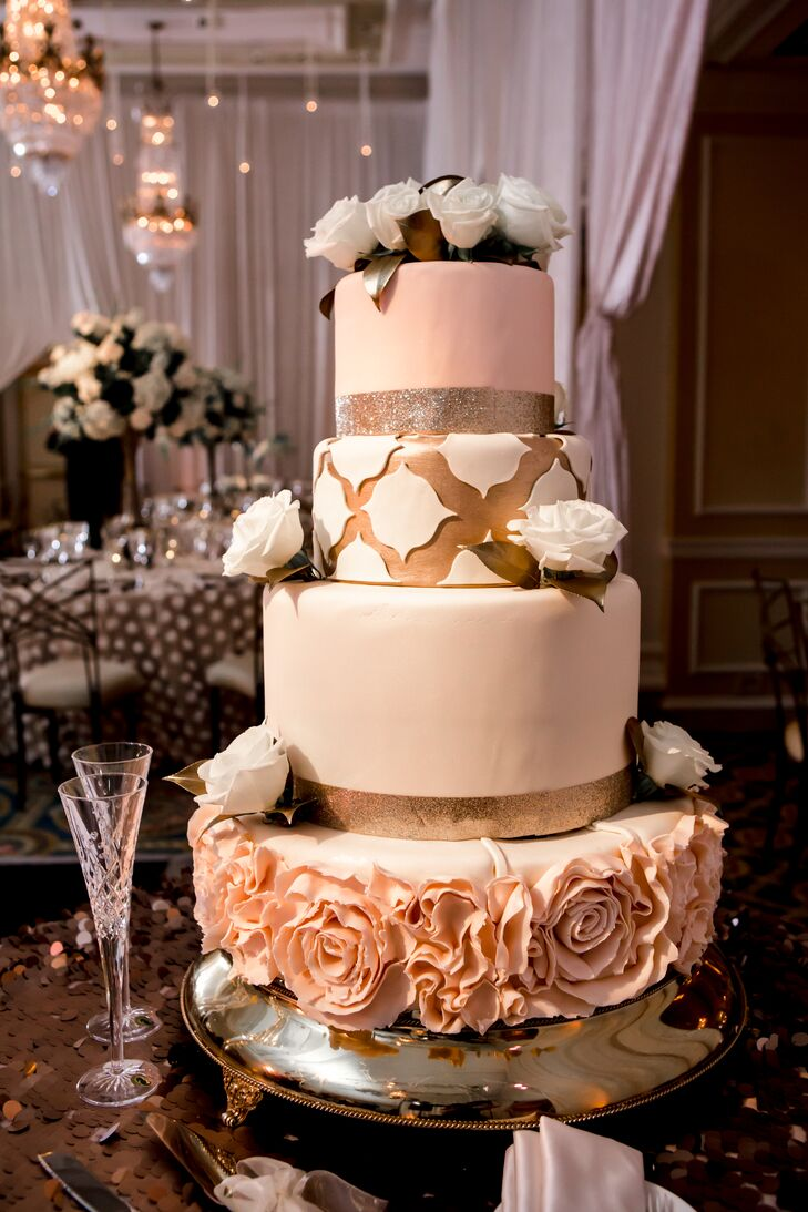 The jaw-dropping wedding cake was decorated with silver and gold ribbons, white roses, blush cake flowers and white and gold fondant. It had two flavors: pistachio pound cake soaked in rum with bittersweet chocolate mousse and apple spice cake soaked in calvados with spiced milk chocolate mousse and chocolate buttercream filling.