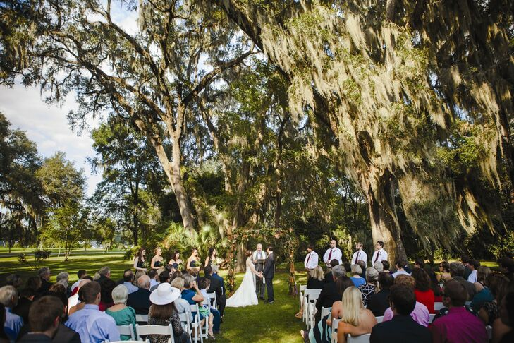 Megan and Louis married under a wooden arch beneath a towering oak tree in the gardens of Southwood House.