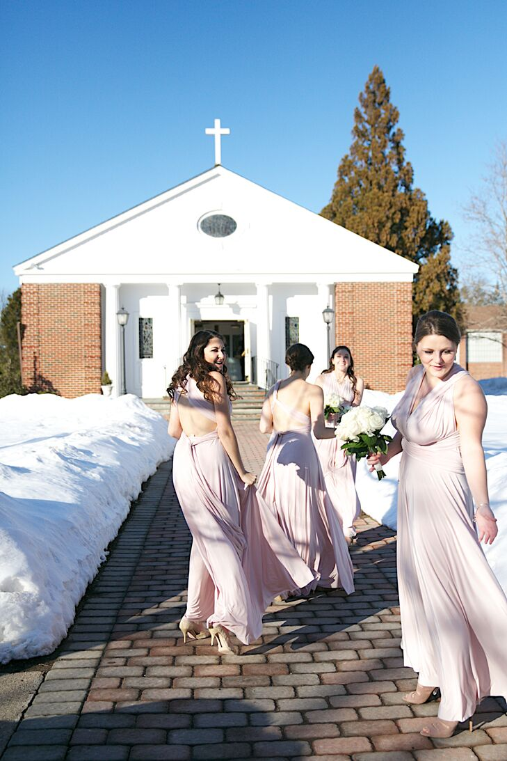 """The bridesmaids wore Dessy blush long twist wrap dresses. """"Not only was a happy because of the color and length, but my girls were also happy because they could style the dress to match their personalities and fashion,"""" Jessica says."""