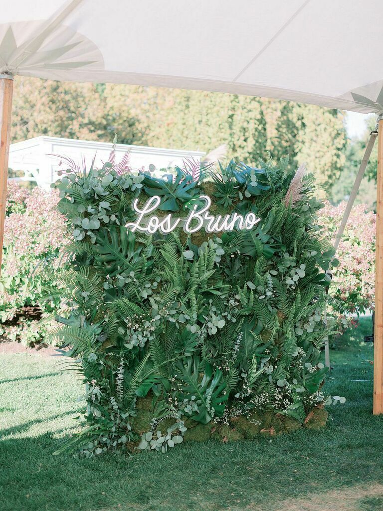 Greenery wall decoration at wedding reception with neon last name sign at top