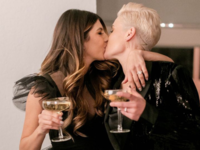 Couple in black wedding attire kissing and holding champagne coupes