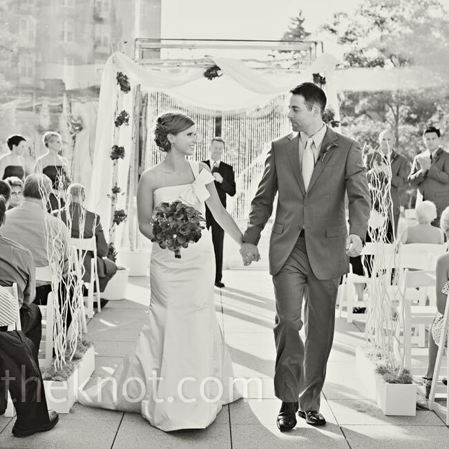 Tall branches lined the aisle and led up to the wall of windows that served as the ceremony backdrop.