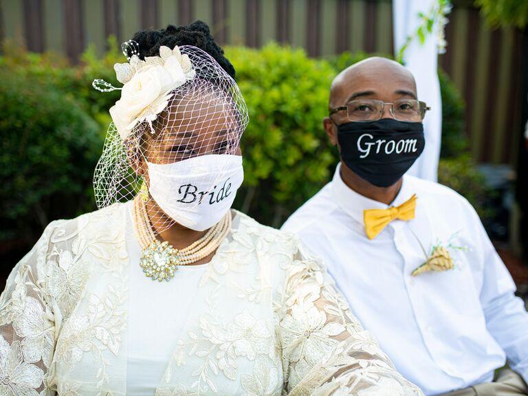 "Bride and groom wearing ""Bride"" and ""Groom"" wedding masks"