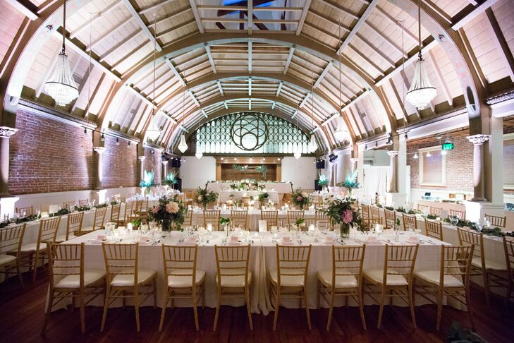 """During cocktail hour, the ceremony site was converted into a romantic reception hall. A combination of round and long communal tables were set with simple white linen and then topped with eucalyptus garlands and glass vases filled with blush dahlias. """"Nestled into the foliage were these beautiful little votives and some tall candlesticks,"""" Alexandra says."""