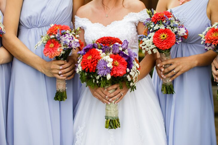 """Kristie and Ryan's wedding was in April, and the bright bouquets made it feel like spring. Kristie and her bridesmaids carried lush arrangements of bright coral dahlias, purple dianthus, purple roses, Queen Anne's lace and greenery gathered in a neutral ribbon wrap. """"We bought our flowers from an Amish woman who grows them on her farm,"""" Kristie says. """"They were absolutely beautiful, and she gave us an awesome price."""""""
