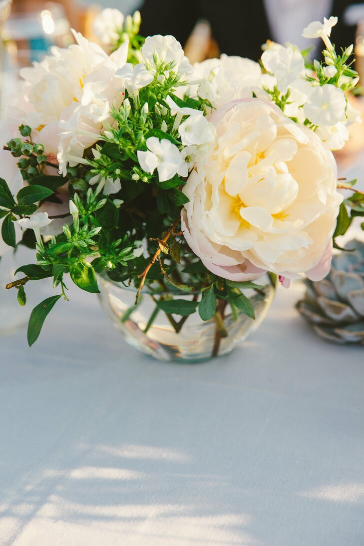 Arrangements of peonies and stephanotises in a variety of glass vases created a romantic, eclectic dinner table.