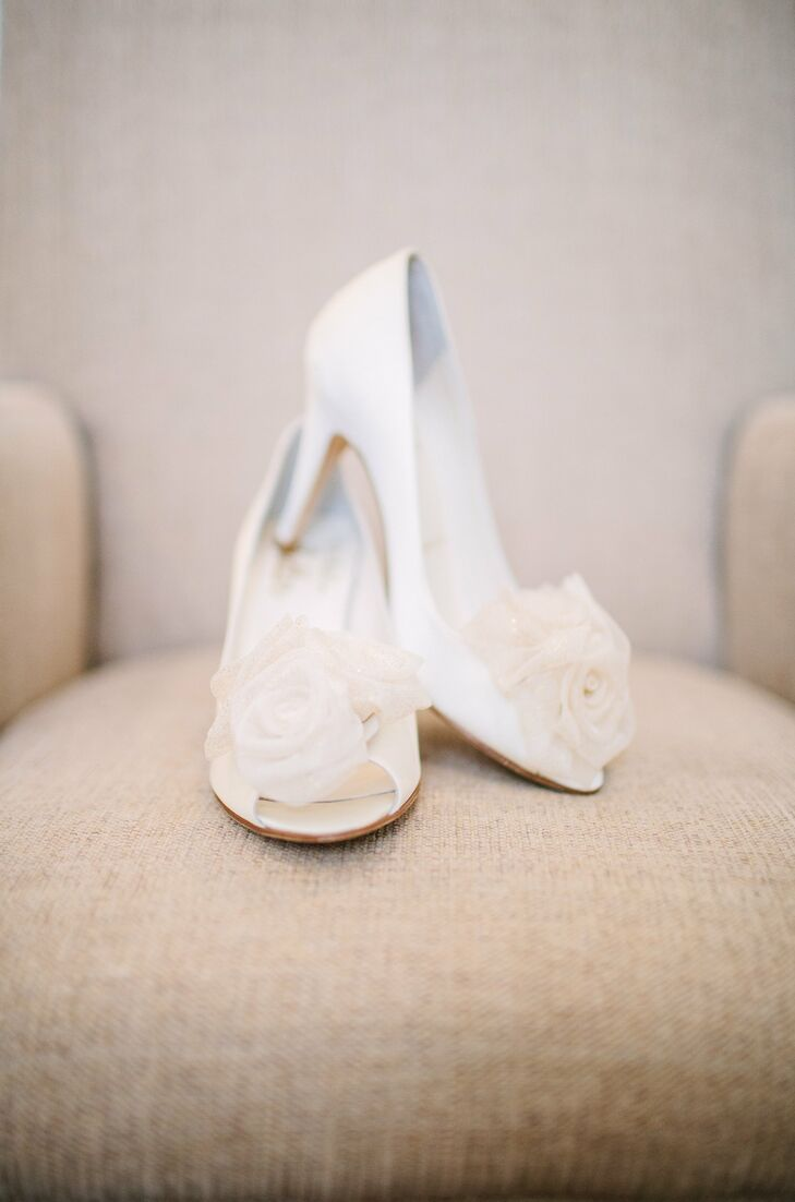 The bride wore ivory satin peep toe heels with a rosette detail on the toe.