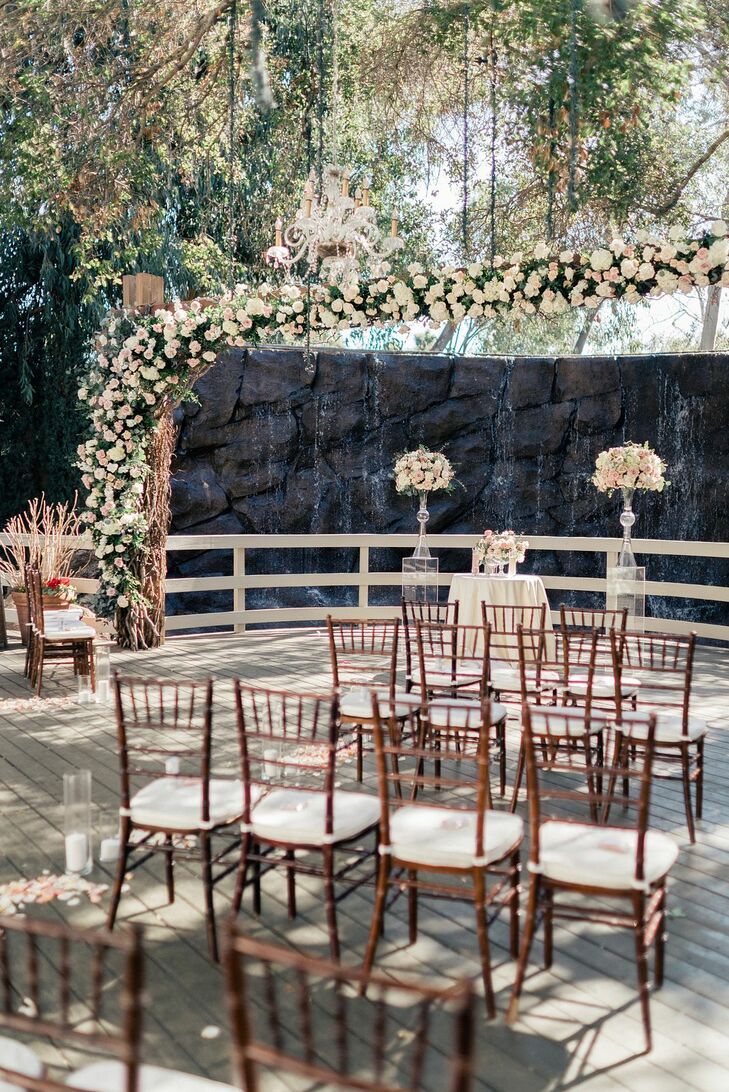 Wedding Ceremony With Rose Altar Arch and Brown Wood Chiavari Chairs