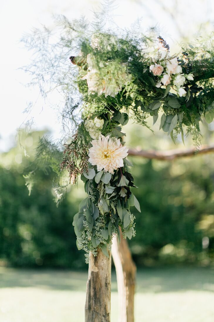"""The birchwood arch under which the couple were married was adorned with eucalyptus, rose, dahlia and greenery, inspired by Heather's experience in Amsterdam, the Netherlands, where she lived for two years. """"Floral arrangements in the Netherlands are often very textured and I wanted to bring that aesthetic to the wedding,"""" she says."""