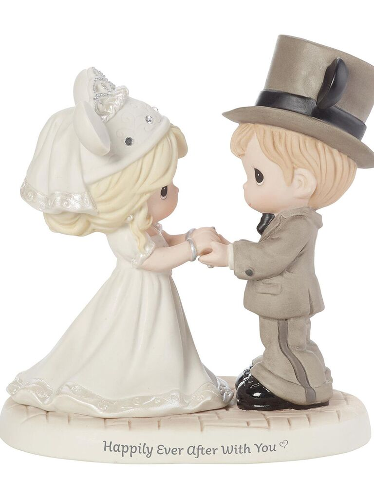 Figurine of couple in wedding attire with Mickey ear accessories holding hands