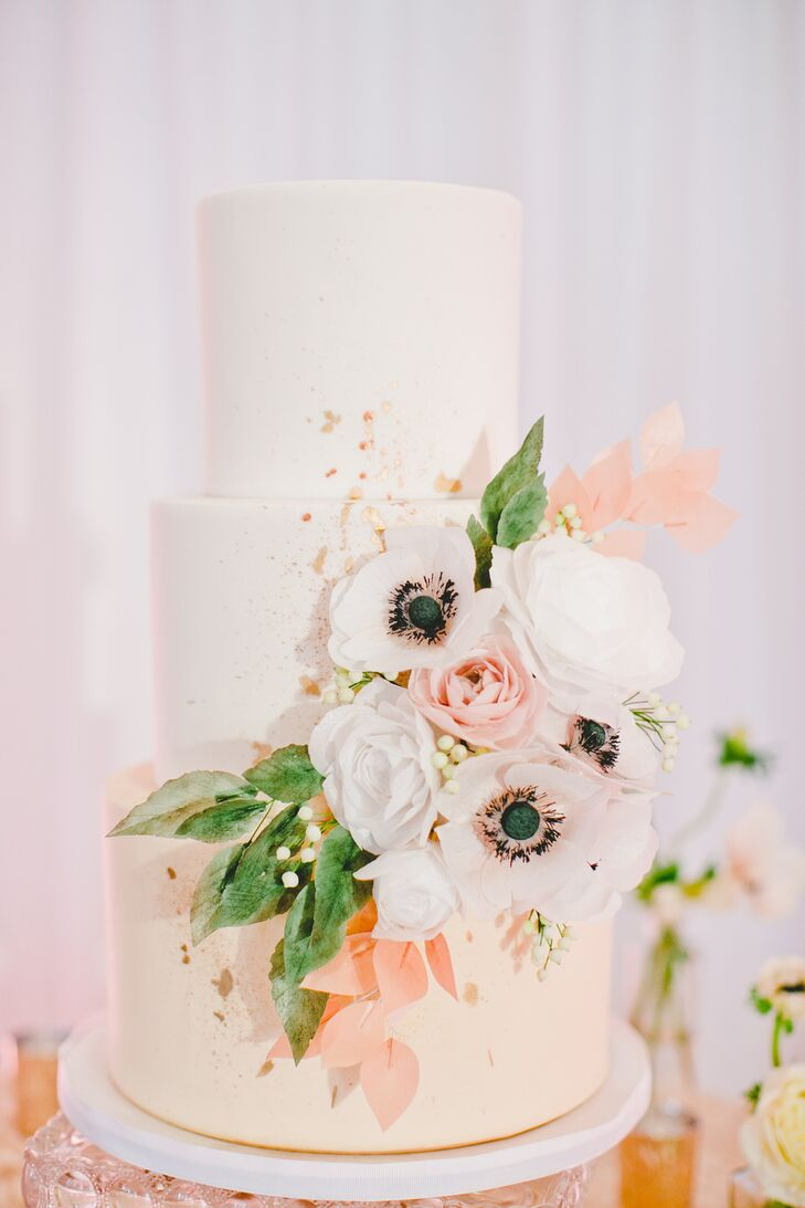 Patricia and Christopher's wedding cake by Heythere, Cupcake! was a confectionary dream. A cascade of anemones, lisianthuses, ranunculuses and greenery decorated the center tier, while the bottom layer was adorned with sparkling rose gold glitter.