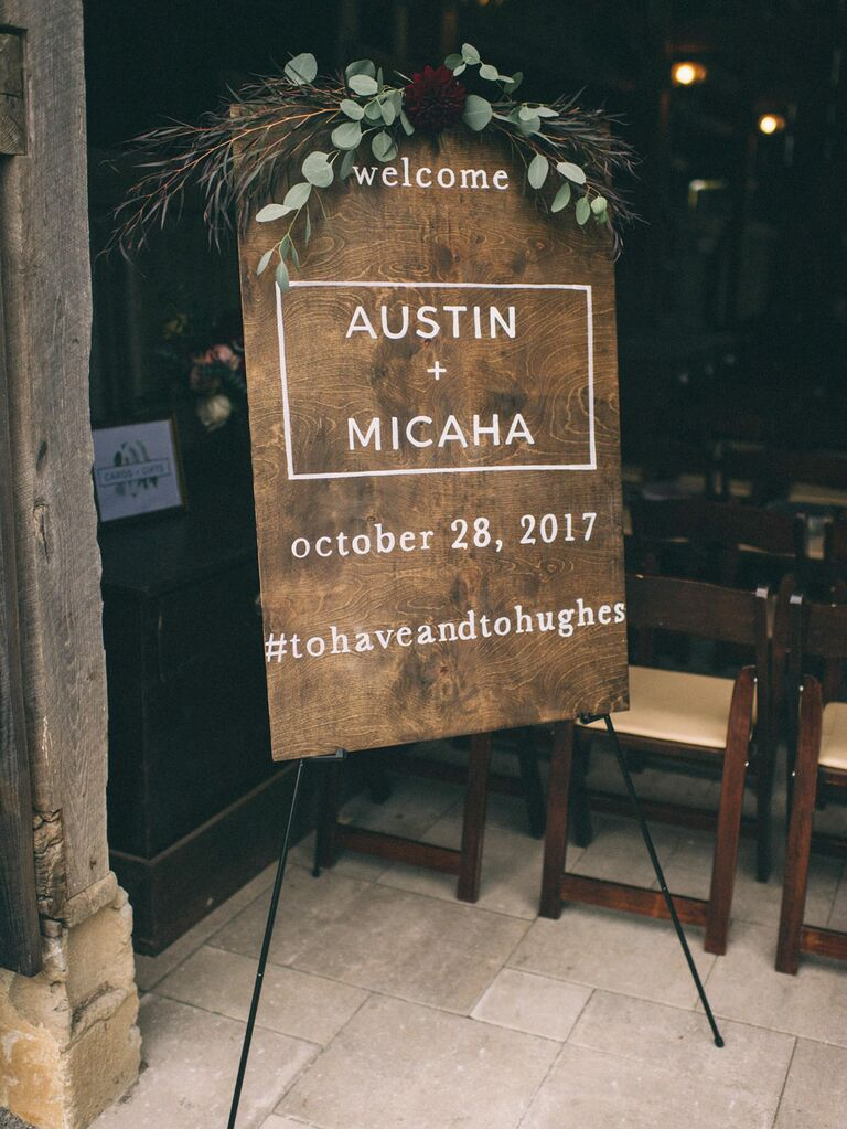 Rustic wood wedding hashtag sign with moody florals