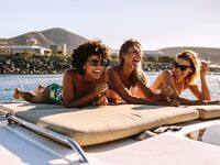 3 women laying out on beach and laughing