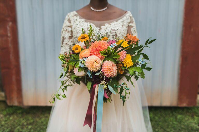 Bride holding colorful dahlia bouquet