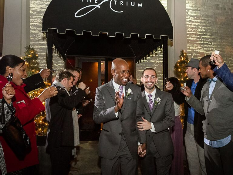 Guests ringing bells as grooms exit wedding reception
