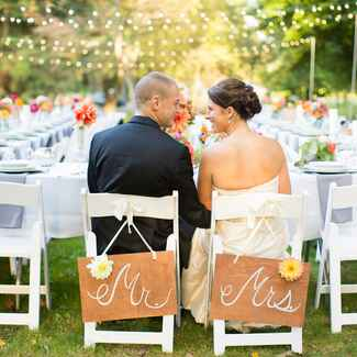 Mr. and Mrs. chair signs at outdoor wedding reception