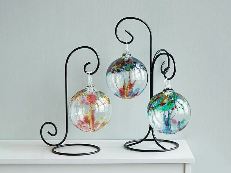 Three colorful recycled glass ornaments hanging on elegant black stand