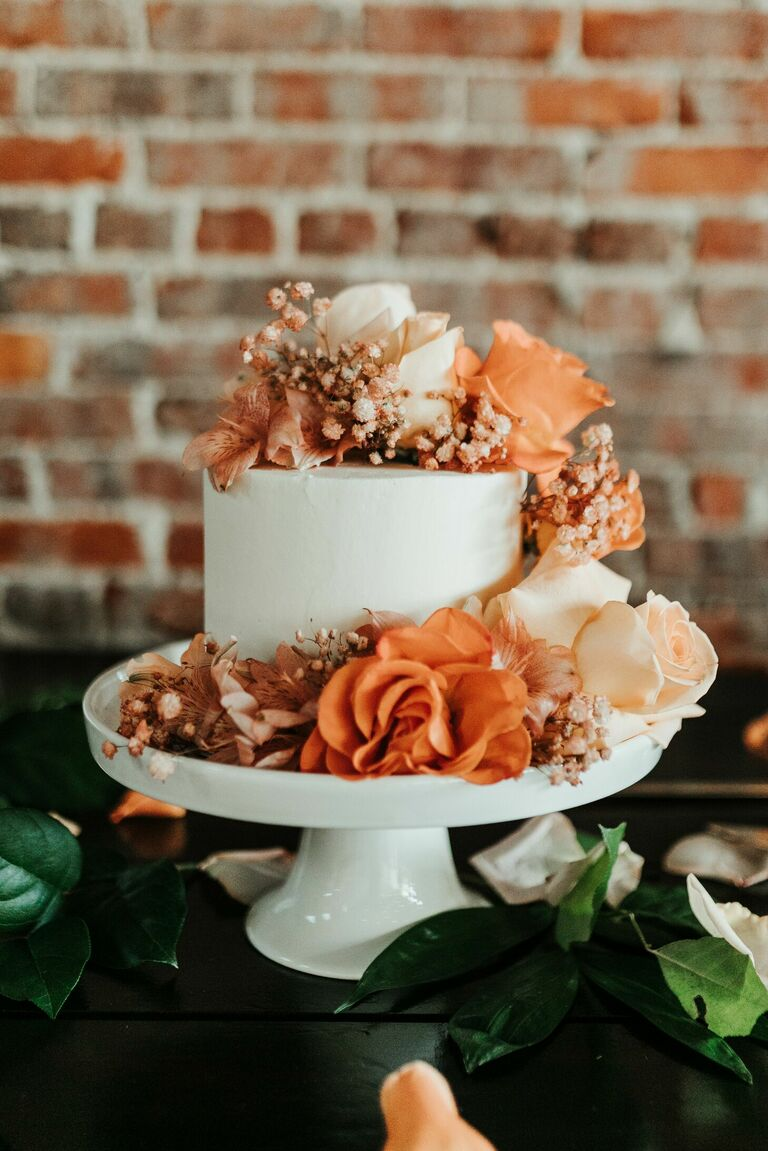 One-tier wedding cake with fresh orange flowers.