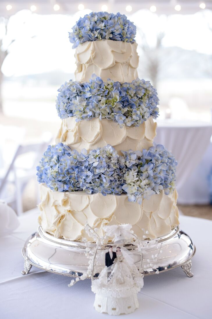 Olexa's Cakes and Catering matched Mary Caroline and Forrest's garden-style wedding with a sweet vanilla and strawberry cake. Blue hydrangeas separated each ivory, buttercream-frosted tier as its bride and groom topper was placed in front of the confection.