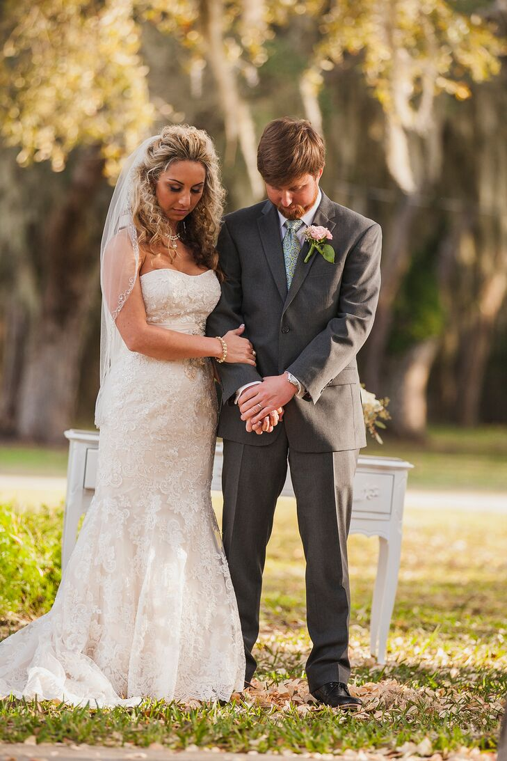 Gina wore a strapless ivory lace mermaid gown by Allure. It was accented with a beaded details and a small ivory sash.