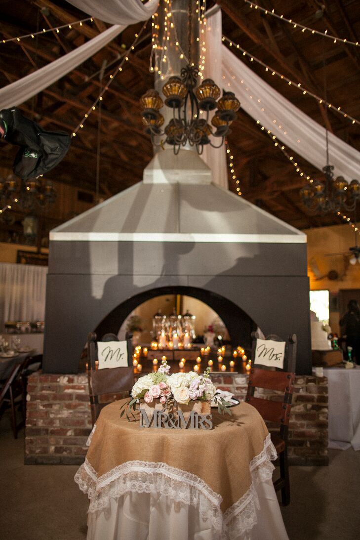 """The couple's sweetheart table was decorated with a burlap and lace tablecloth, """"Mr. & Mrs."""" sign and a low rose arrangement in pastel colors."""