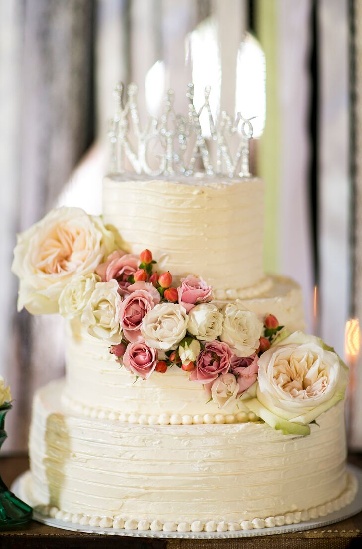"""The couple chose a four-tier confection decorated with cascading garden roses in various hues. It was topped with a custom silver """"Ingram"""" accent."""