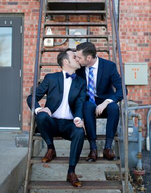 Two Groom's in Navy Suits Kiss Outside Alex Johnson Hotel