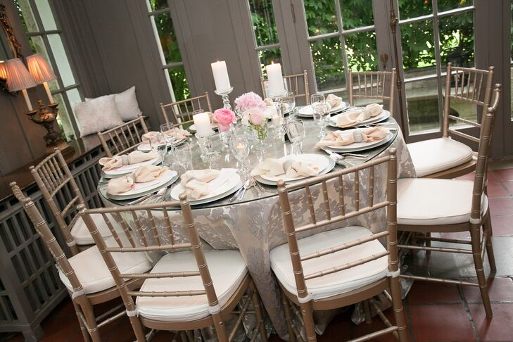 White candles and small pink floral arrangements added to the soft, romantic atmosphere at the reception.