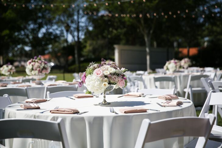 Lidia and Nick decorated their reception tables with vintage silver vases holding ivory hydrangeas, blush roses, white ranunculus and stock. Lidia and Nick loved how the centerpieces added a little glamour, fit in with the vintage theme and provided a pop of color against the neutral linens.