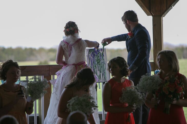"""Instead of a traditional unity candle, the couple had a unity painting where they poured paint on a canvas together. """"Although painting on a windy day in a wedding dress was a bit risky, it was a special moment and provided a wedding day memory that we can hang in our house,"""" Mandy says."""