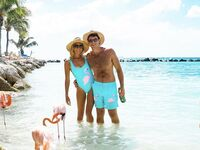 Couple wearing matching turquoise flamingo one-piece swimsuit and trunks