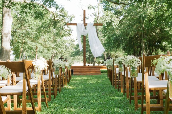The ceremony took black under rows of lush trees at Sarah's family home. The aisles were decorated with simple bouquets of baby's breath arranged in mason jar vases. The ceremony altar and cross were specially made for the event by one of the ranch hands.