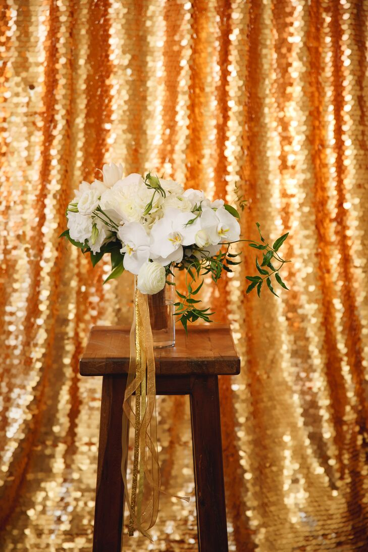 Tied with flowing gold ribbons, the asymmetrical bridal bouquet included a loose blend of white roses, ranunculuses, orchids, peonies and tulips.