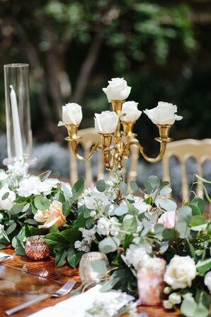 Roses Displayed in Gold Candleholder Among Eucalyptus
