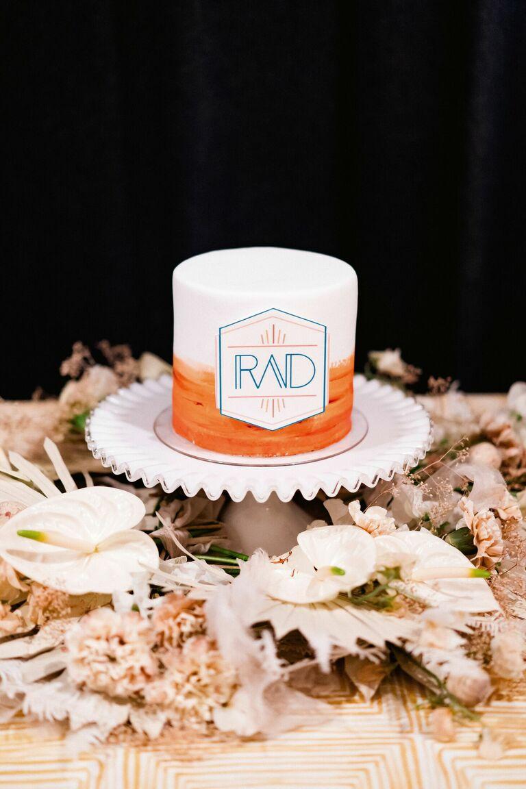 One-tier orange-and-white cake with modern monogram
